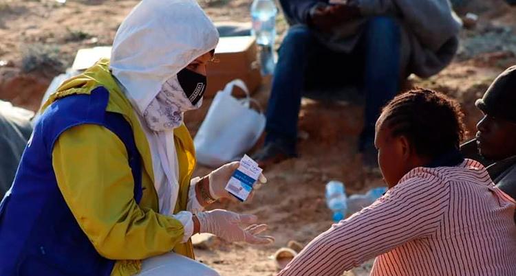 En kvinna pratar med en annan kvinna. De är på en strand.