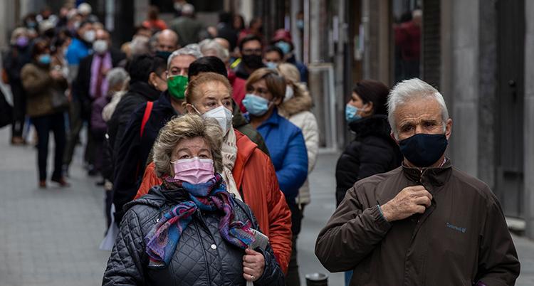 Människor går på en gata. Alla har munskydd.