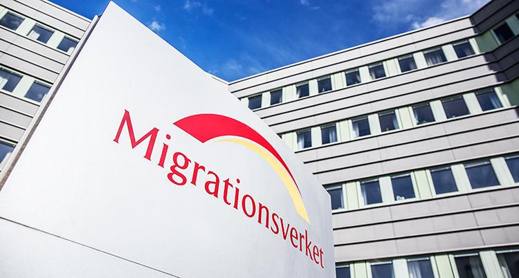En skylt som det står Migrationsverket på i rött syns i förgrunden. Den är utomhus och syns mot en vit husfasad med många fönster och en blå himmel