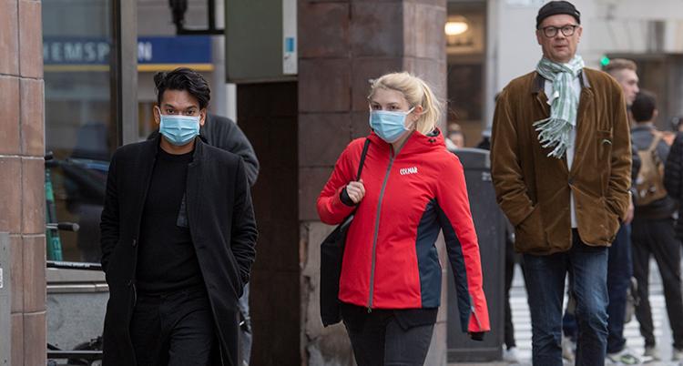 Människor går på en gata. En man och en kvinna har munskydd. En man bakom dem har inte.