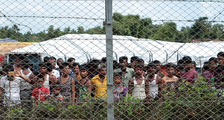 Många rohingyer i ett läger, bakom gallerstängsel.