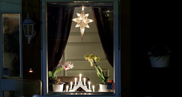 Ett fönster med en julstjärna och en ljusstake.