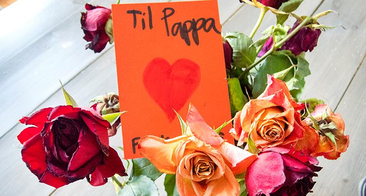 en blombukett med rosor i olika färger och ett orange kort i buketten med texten Til Pappa