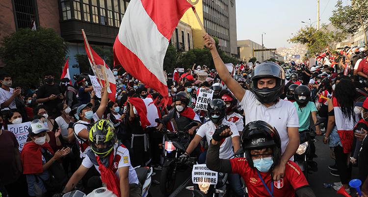 En massa människor trängs på en gata. De håller upp flaggor och skyltar. Flaggan är röd och vit. En del håller upp knutna nävar.