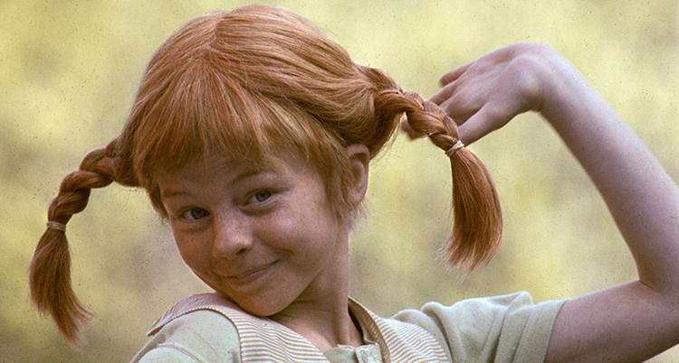 En flicka med röda flätor som står rakt ut sätter sin vänstra hand bakom huvudet