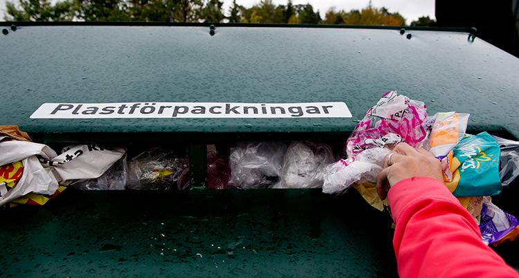 En hand slänger plast i en stor grön container för återvinning.