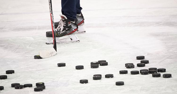 En massa ishockeypuckar ligger på isen och en person med skridskor och ishockeyklubba står bakom puckarna