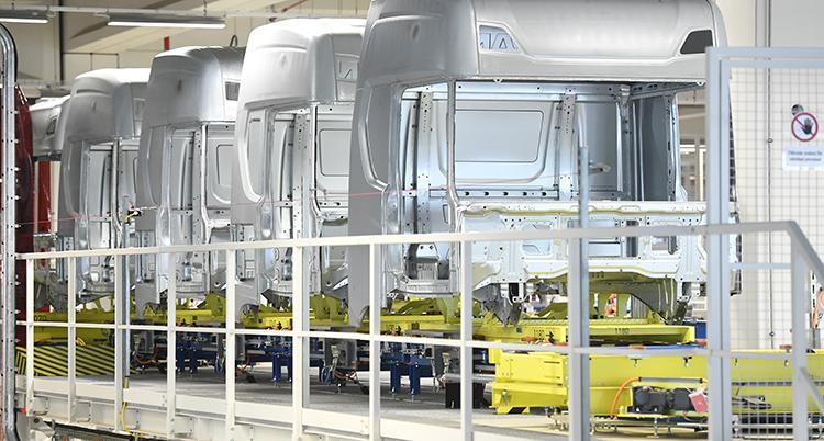 Grå karosser till lastbilar i rad i en fabrik där de håller på att tillverkas