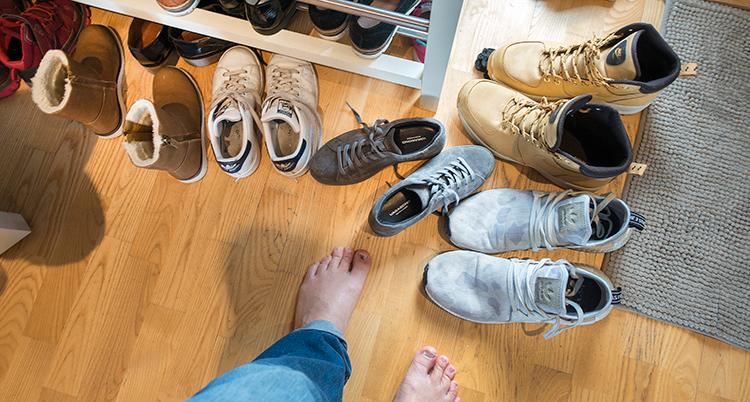 En person med bara fötter står på ett trägolv framför en stor mängd skor och kängor.