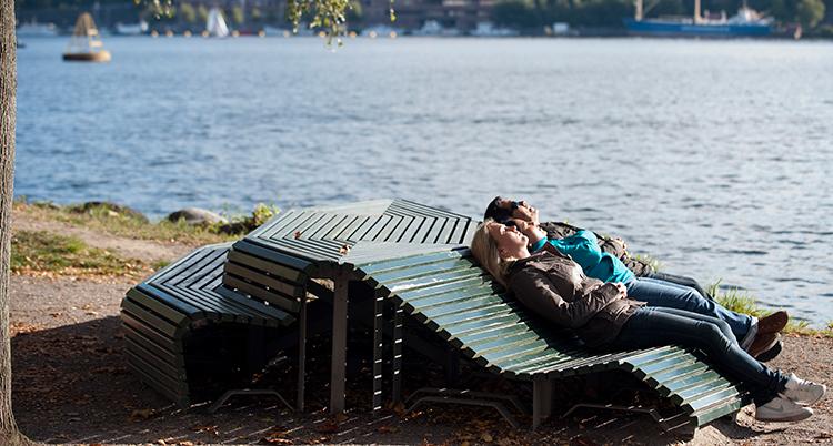Två personer ligger på en bänk utomhus och solar.