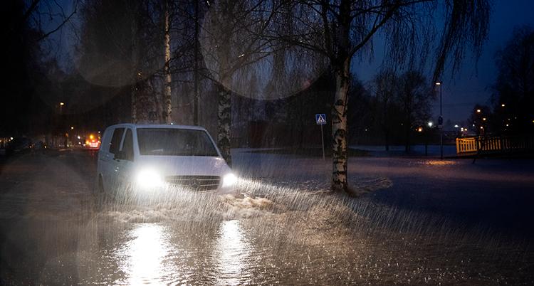 En bil kör genom en väg som är översvämmad. Det är mörkt ute och genom billyktornas sken ser vi att det regnar.