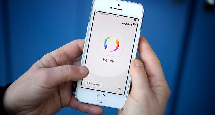 två händer håller i en mobil som visar appen swish.