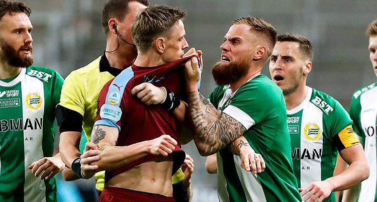 en fotbollsspelare i grön tröja ser arg ut och tar ett hårt tag om en annan fotbollsspelares tröja