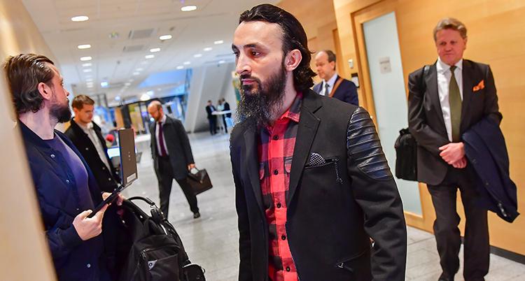 En man med mörkt hår och mörkt helskägg, klädd i röd skjorta och svart jacka, är på väg in i en rättegångssal.