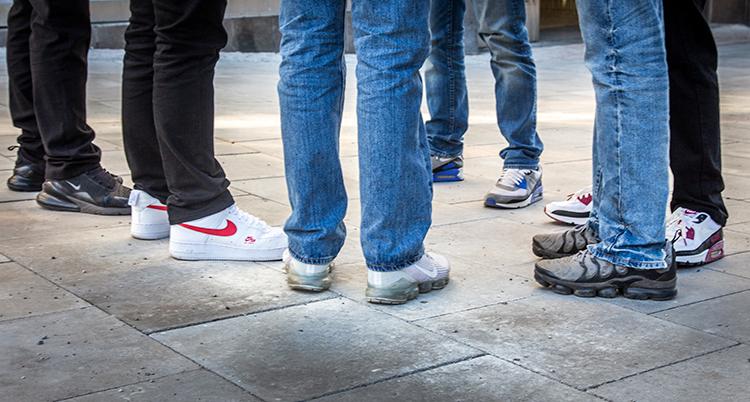Sex unga jeansklädda benpar syns i en grupp, alla bär sneakers.