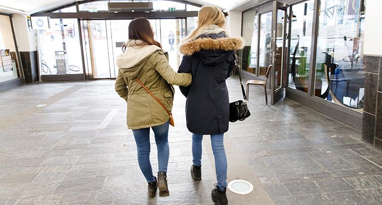 Två unga kvinnor går tillsammans. Vi ser deras ryggar.