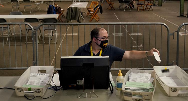 En man med munskydd sitter vid ett bord. Han sträcker sig fram och lägger en lapp i en låda. Han har tre lådor framför sig och en dator.