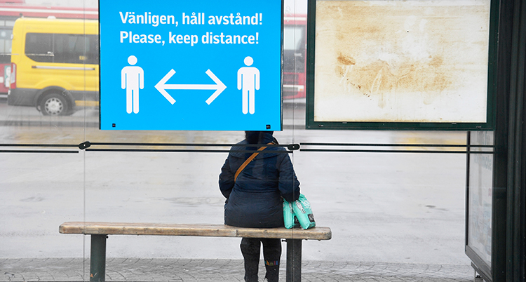 En person sitter ensam på en bänk i en busskur. På busskuren finns en stor skylt som visar att vi ska hålla avstånd.