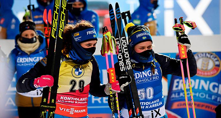 Hanna och Elvira står bredvid varandra. De håller i sina skidor och stavar. De är glada. De har munskydd på sig.