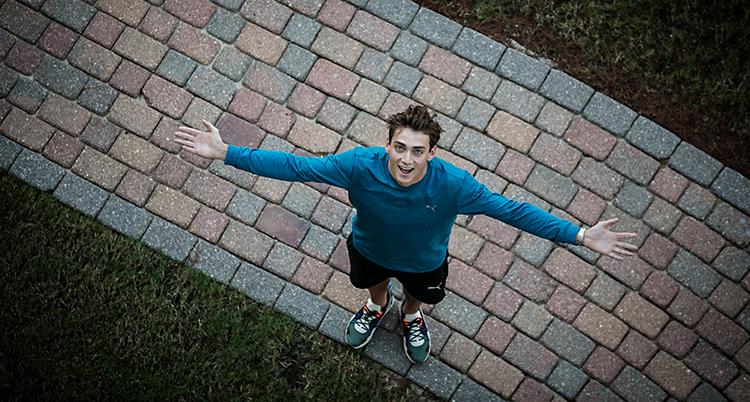 Bilden är tagen uppifrån, kanske från en balkong. Nere på marken står Armand Duplantis. Han tittar upp mot kameran och ler. Han sträcker ut armarna.