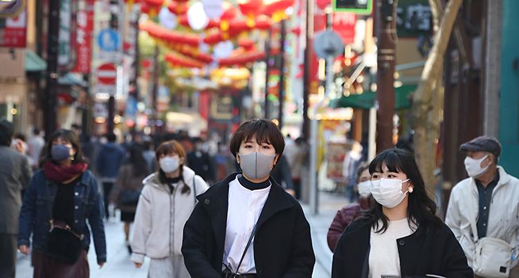 Människor går på en gata i staden Yokohama. Längst fram ser vi två unga kvinnor. De har munskydd på sig.