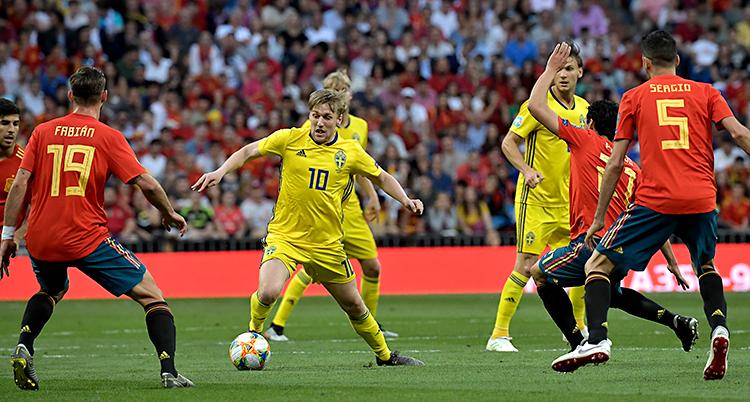 Sveriges herrar spelar en match mot Spanien i fotboll. Den svenska spelaren Emil Forsberg har bollen. Han har gula kläder. Spaniens spelare har röda kläder.