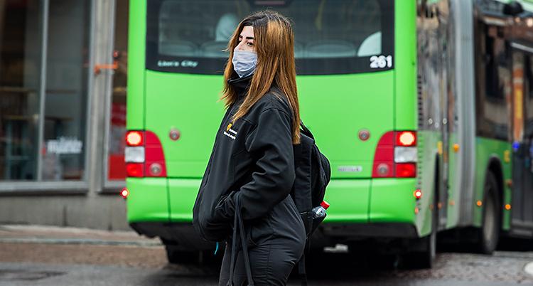 En kvinna går över en gata. Hon har ett munskydd på sig och svarta kläder. Bakom henne kör en grön buss.