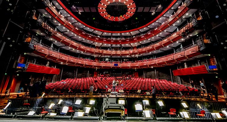 En bild på Göteborgsoperans stora salong tagen från scenen. Det ser maffigt ut med tända lampor i taket och röda sammetsklädda stolar. Salen är tom.