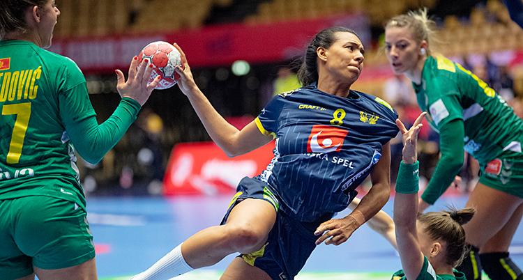 Det är en match i handboll. Jamina Roberts från Sverige försöker skjuta ett skott. Hon har blå kläder. Det andra laget har gröna kläder.