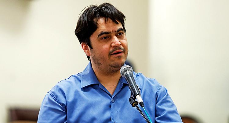 Bilden är tagen i en sal där det är en rättegång. Ruhollah Zam pratar i en mikrofon. Han har svart hår och en blå skjorta.