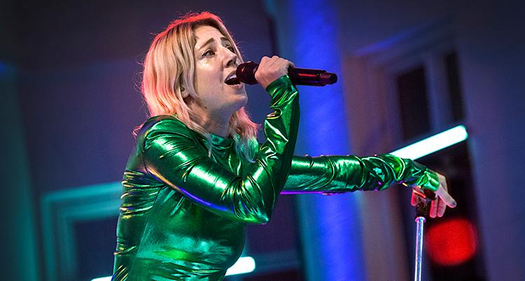 Hon står på en scen och sjunger i mikrofon. Hon har gröna kläder som glänser.