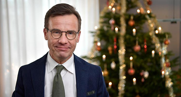Ulf Kristersson tittar in i kameran. Han har glasögon och kostym. I bakgrunden står en julgran.