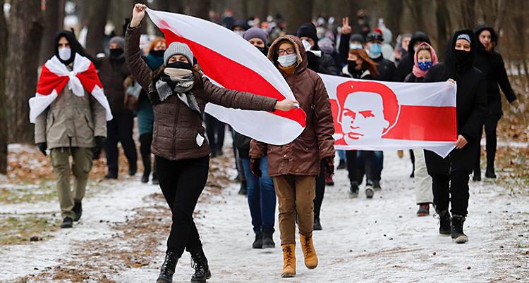 Människor går på en väg. Det är lite snö på vägen. Människor har flaggor i rött och vitt. De har munskydd på sig.