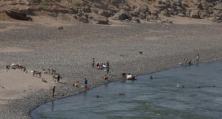 Bilden är tagen från en kulle ner mot en flod. Där syns människor som simmar i vattnet. På ena sidan floden sitter och står människor.