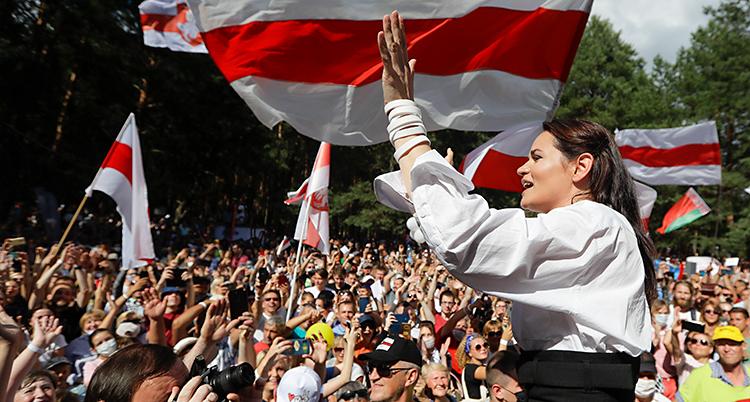 Svetlana står och vinkar. Framför henne står en stor massa med människor. De hejar på henne. De har flaggor som är röda och vita.