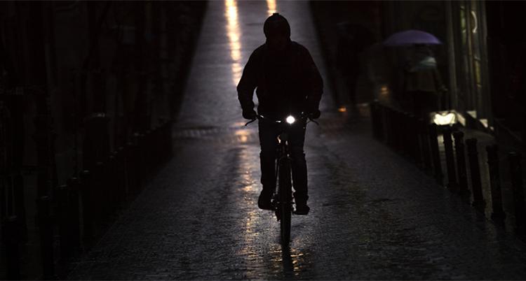 Det är mörkt ute. En person kommer cyklande mot kameran. Det är ett lyse tänt på cykeln.
