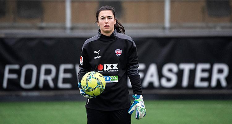 Hon står på en fotbollsplan. Hon har handskar på sig. Hon håller i en fotboll.