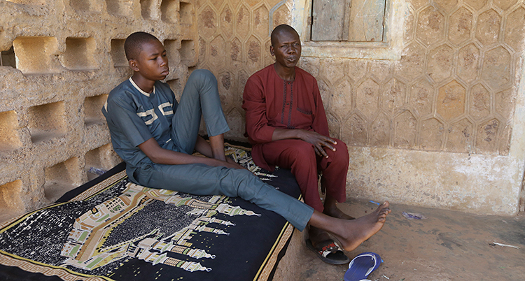 Bilden är tagen i landet Nigeria. En 17-årig pojke sitter på en säng. Han har en blå tröja och blå byxor. Bredvid sitter hans pappa som har röda kläder.