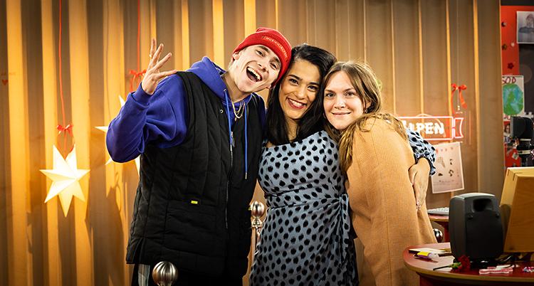De står i en radiostudio. Felix står till vänster, Farah i mitten och Brita till höger. De är glada och tittar in i kameran.