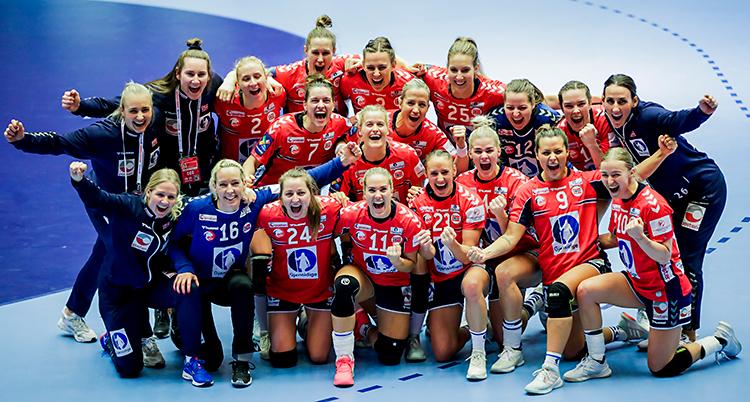 Bilden är tagen inomhus i en sporthall. Vi ser Norges lag i handboll för damer. Alla är samlade på en bild. De jublar och är glada. De har röda kläder.
