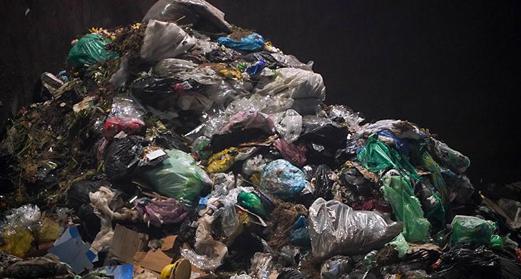Bilden visar en stor hög med sopor. Det är plastpåsar i olika färger och massa skräp.