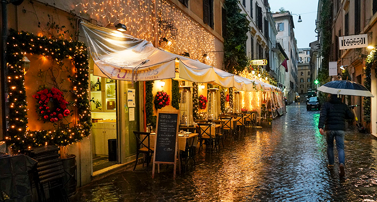 En man går på en tom gata förbi en restaurang med julbelysning.