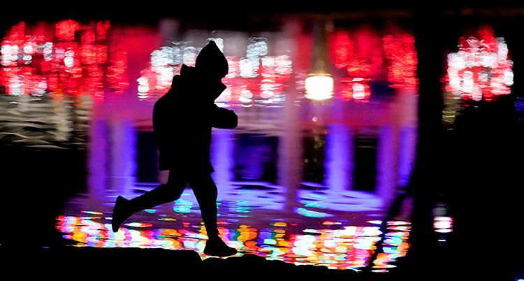 Ett barn springer genom mörker där en vattenpöl speglar många färger