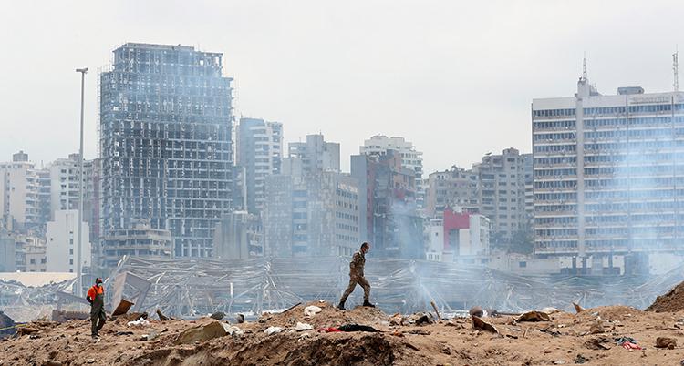 En man går över en hög med sand och bråte. Det ryker. Bakom honom är en rad med förstörda höga hus.