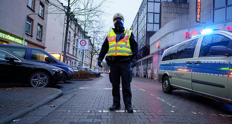 En polis i gul varselväst står mitt i gatan, en polisbil passerar till höger