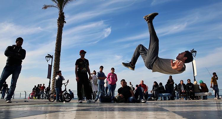 En man dansar breakdance och hoppar i luften med ett ben mot himlen. Han dansar utomhus och bakom honom syns många människor som sitter och står och tittar