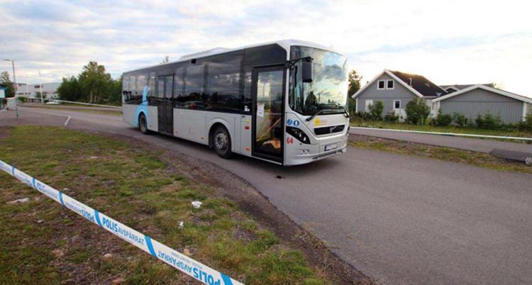 Polisens avspärrningsband framför en vit buss som står på en landsväg