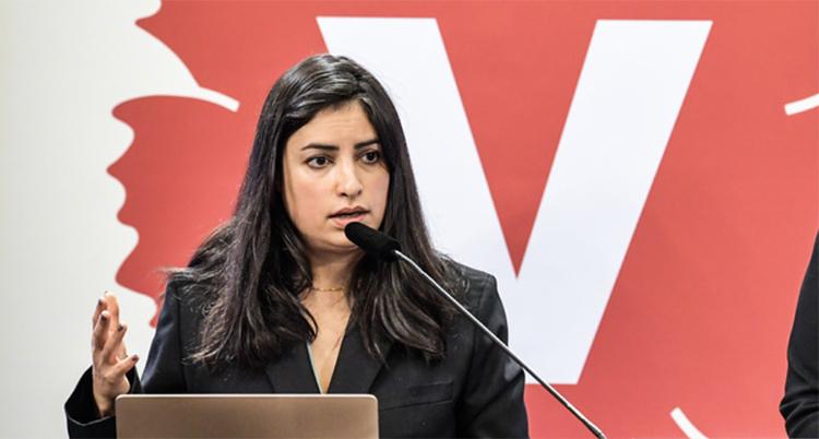 Hon står i en talarstol och pratar i en mikrofon. Bakom henne är partiets symbol ett V.