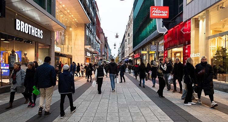 Människor som går på en gågata med butiker längs sidorna