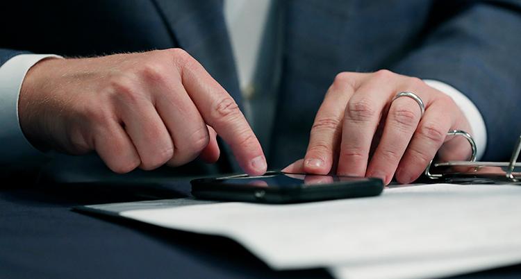 Man ser händerna på en person som knappar på en mobil